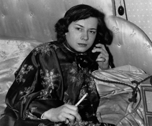 "Patrica Highsmith, 27, is seen phoning from her London apartment, Feb. 16, shortly after her arrival from America. Her first novel ""Strangers on a Train"" was acclaimed by American critics and a film of the book is now being made in Hollywood. (AP Photo)"